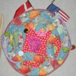 Dot White created a round quilt to represent her world and her passions in life.  Beside the American flag is the Denmark flag, Dot's country of origin.  Dot embelished her quilt with stuffed Japanese Koi Fish.