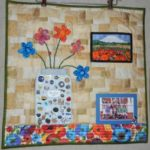 """Julie Howell created a wall quilt centered around the blessings in her life.  Her family is featured in the photo at the top right.  Included in her """"blessings jar"""" are buttons, pins, and other memorabilia.  Julie used her folded flower method to add dimension to the jar of flowers."""